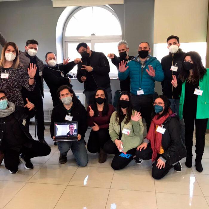 Grupo de trabajadores hombres y mujeres en reencuentro profesional post covid 19